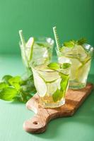 mojito cocktail en ingrediënten op groene achtergrond foto