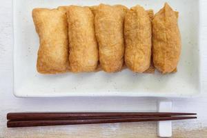 gekookte rijst met sushismaak verpakt in gebakken tofu foto