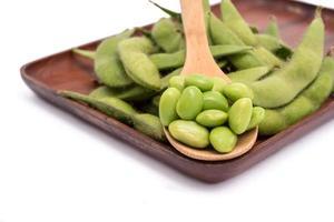 groene sojabonen op houten dienblad dat op witte achtergrond wordt geïsoleerd