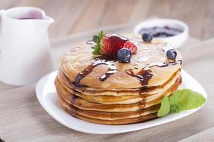 heerlijke zoete Amerikaanse pannenkoeken op een bord met vers fruit foto