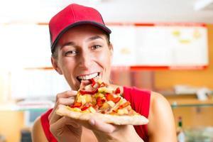vrouw eet een stuk pizza foto