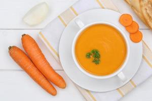 wortelsoep met verse wortelen in kom van bovenaf foto