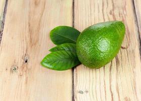 rijpe groene avocado met bladeren op houten achtergrond. foto