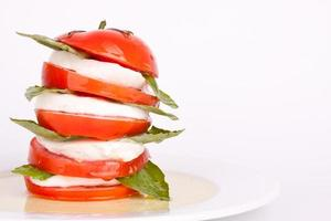 caprese salade met mozzarella, tomaat en basilicum foto