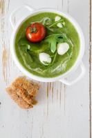 groene pure soep met rucola en tomaat in witte kom