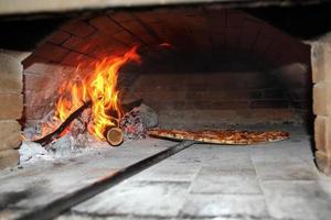 pizza bakken in een houtgestookte oven foto