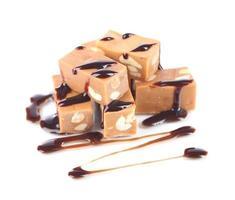 veel toffee met chocolade op wit wordt geïsoleerd foto