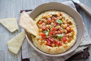 hummus met een salade van tomaat, ui en koriander foto