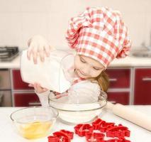 lachende meisje met chef-kok hoed zet meel foto
