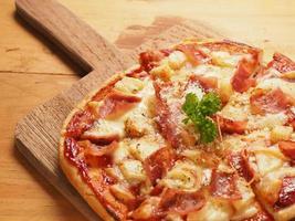 Hawaiin pizza op houten plaat foto
