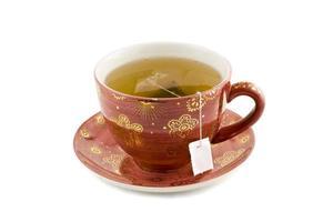 lekker kopje thee in een rood vintage set theekopje en bord foto