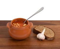 soep in klei pot met brood en knoflook op tafel foto