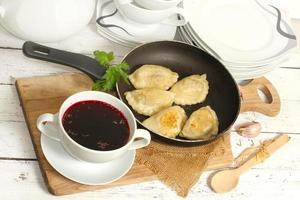 huisgemaakte pierogi (ravioli) en helderrode borsjt foto