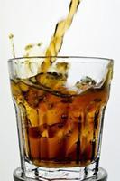 cola wordt in een glas gegoten foto