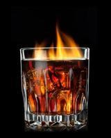 cola met cognac en vuur in glas op zwart foto