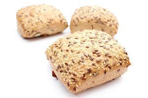 verse volkoren broodjes die op witte achtergrond worden geïsoleerd foto