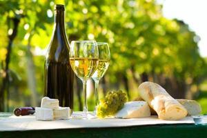 twee glazen witte wijn en fles foto