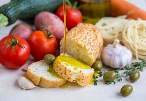 extra vergine olijfolie op wit stokbrood en groenten foto