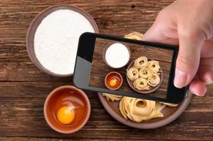 handen nemen foto pasta met smartphone.