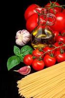 rauwe pasta geïsoleerd op zwarte tomaten, olijfolie, knoflook foto