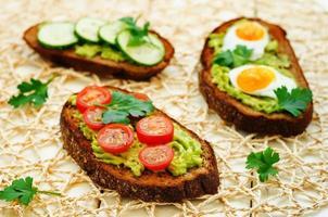 roggesandwiches en gepureerde avocado, eieren, tomaten en komkommers foto