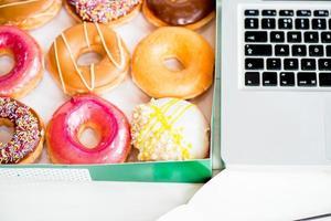 snack van geglazuurde donuts in de buurt van laptop op bureau foto