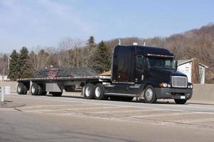 geladen flatbed zwarte semi vrachtwagen foto