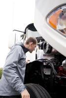 vrachtwagenchauffeur die de witte grote motor van de tuig semi vrachtwagen inspecteert foto