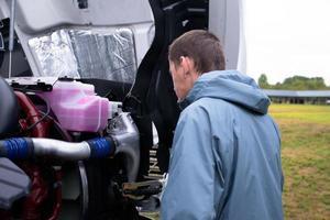 vrachtwagenchauffeur controleer semi-vrachtwagenmotor alvorens semi-vrachtwagen te drijven foto