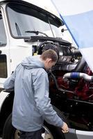 vrachtwagenchauffeur die de semi vrachtwagen van de verrichtingsmotor met open kap controleert foto
