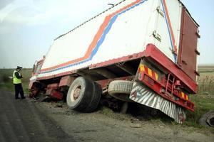 vrachtwagen die in een greppel ligt met het onderzoeken van de politieagent foto