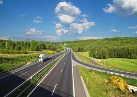 toegangsweg naar de asfaltweg tussen bossen. witte vrachtwagen. foto