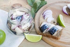 plakjes gemarineerde makreel met ui in een pot foto