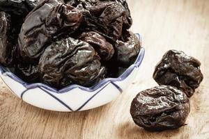 gedroogde pruimen pruimen in kom op houten tafel foto