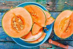 gesneden rijpe meloen op een plaat op een rustieke achtergrond foto