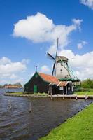 Nederlandse windmolen over rivierwater foto