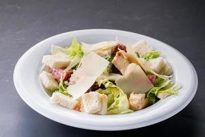Caesar salade met kip en Groenen op houten tafel foto