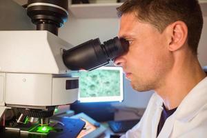 wetenschapsstudenten die door microscoop kijken foto