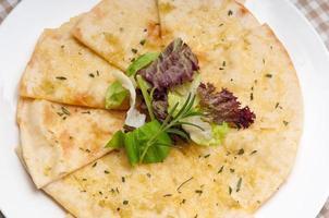 knoflook pitabrood pizza met salade bovenop foto