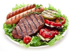gegrilde biefstuk, worstjes en groenten. foto