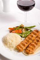 kip adana kebap geserveerd met rode wijn foto