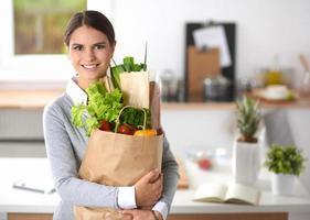 jonge vrouw met boodschappen tas met groenten staan in