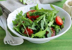 salade met rucola en tomaten geserveerd op een houten tafel