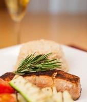 gezwarte zalm met bruine rijst en gegrilde groenten foto