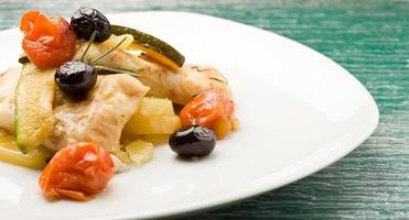 gebakken kabeljauw met olijven en tomaten foto