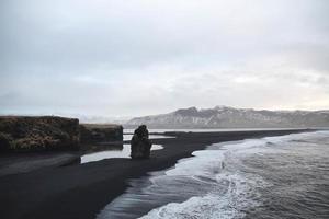 eenzame rots op zwart strand foto