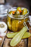 augurken met knoflook in glazen pot op rustieke houten achtergrond foto