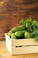 verse biologische komkommers in een houten kist foto