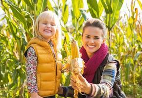 gelukkige moeder en kind dat graan toont terwijl in korenveld foto