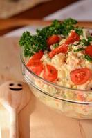 zelfgemaakte aardappelsalade met eieren en augurken in glazen kom foto